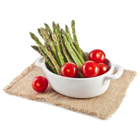 Asparagus and cherry tomatoes in pot isolated on a white background photo