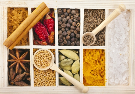Assortment collection of powder spices on spoons in wooden box background photo