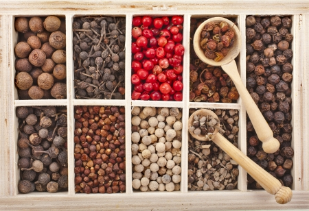 Assortment of different peppercorns in wooden box photo