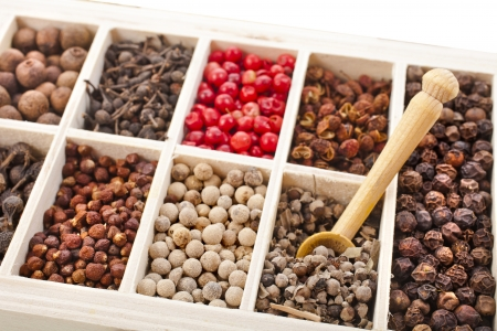 Assortment of different peppercorns in wooden box isolated on white photo