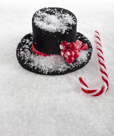 black top hat snowman with Cane on white snow background photo