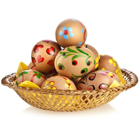 Painted colorful easter eggs in basket dish, isolated on white background photo