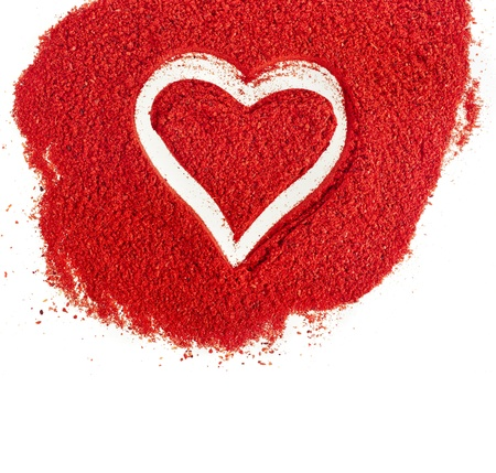 ground paprika with shapes heart sign on white background photo