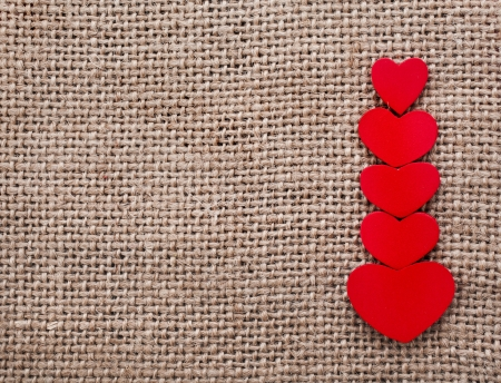 wedding wishes: Valentine s day card with wooden red hearts symbol on fabric sack texture background Stock Photo