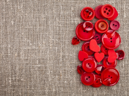 Border of red buttons and hearts on canvas burlap background texture photo