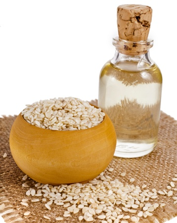 Sesame seeds and glass oil isolated on white background photo
