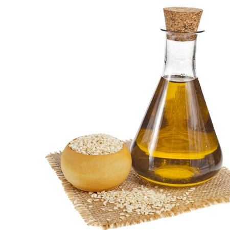 Sesame seeds and glass oil isolated on white background Stock Photo