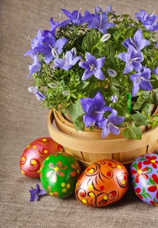 border card , blue flowers in basket with colorful easter egg on canvas sack texture background photo