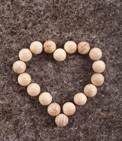 Heart made of wooden balls on wool felt texture background Stock Photo - 18730892