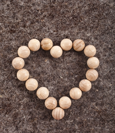 Heart made of wooden balls on wool felt texture background Stock Photo - 18730892
