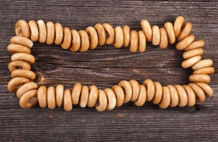 boublik: Border frame of sheaf bagels on old ancient wooden texture Stock Photo