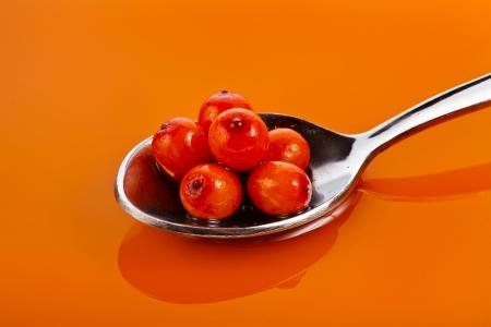 sea-buckthorn oil on tea spoon background photo