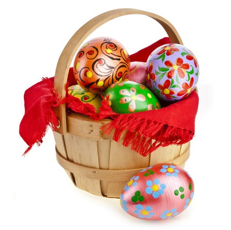 Painted colorful easter eggs in wooden basket , isolated on white photo