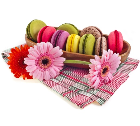 Colorful macaroons in a bowl with gerbera isolation on a white background Stock Photo - 18932182