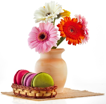 Colorful macaroons and bouquet gerber in vase isolation on a white background