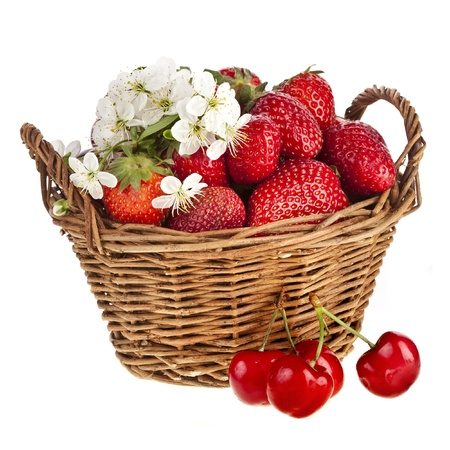 Sweet strawberry and cherries with flowers in basket isolated on white background photo