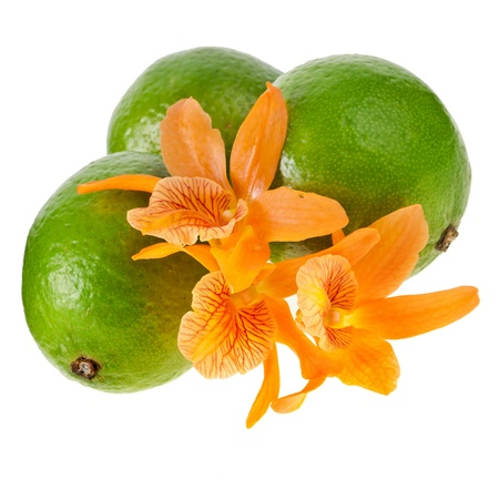 Green limes with orchids close up isolated on a white background photo