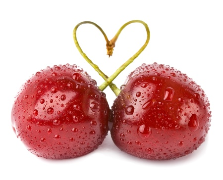 allegiance: two cherries with drops tied into a heart love isolated on white background Stock Photo