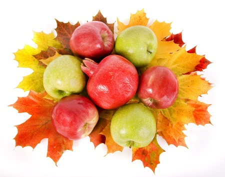 apple and pomegranate on the autumn leaves isolated on white background photo