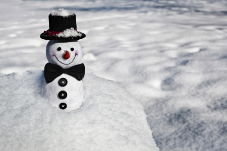 Happy Christmas snowman sitting in a snowy hill outdoors photo