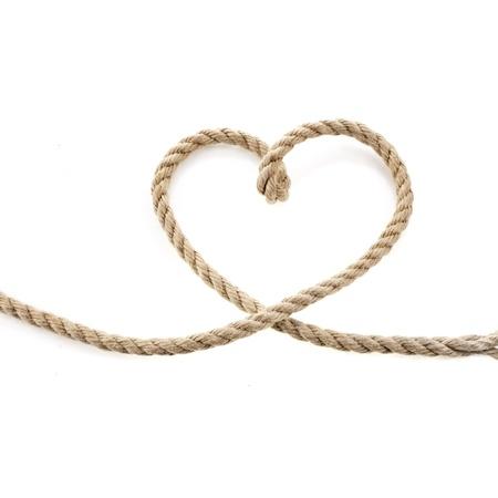 白い背景で隔離されたジュート ロープの上の心形の結び目