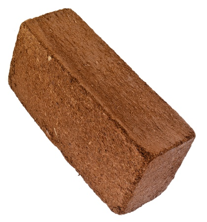 turba: A una cuadra de briquetas de fibra de cáscara de coco aisladas sobre fondo blanco