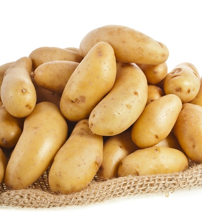 Raw potatoes heap with sack cloth close up isolated on a white background photo