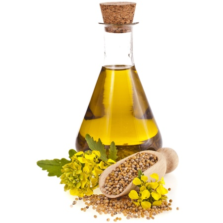 mustard plant: oil glass jar , seeds,and mustard flower blossom isolated on white background