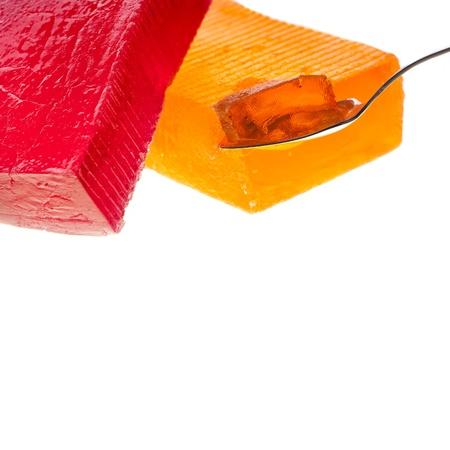 GELATIN: fruit jelly on tea spoon close up macro isolated on white background