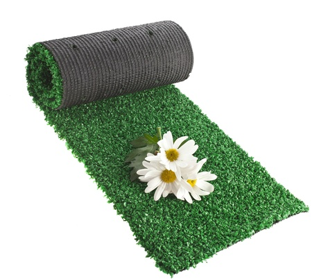 artificial rolled green grass for cover sports field with flowers isolated on white background photo