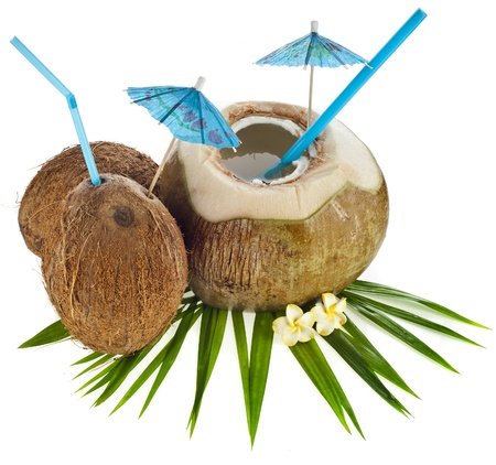 Coconut drink with a straw and palm leaf isolated on white background photo