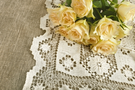 Wedding card with bunch of fresh cream roses on canvas texture with retro crochet doily photo