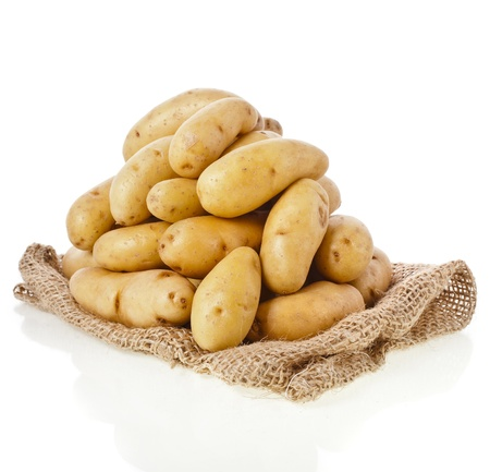 Raw potatoes heap with sack cloth isolated on a white background photo