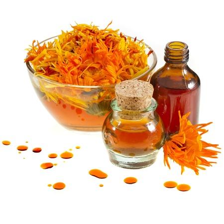 calendula hierbas en el vaso y aceite esencial de aromaterapia aislado fondo blanco Foto de archivo