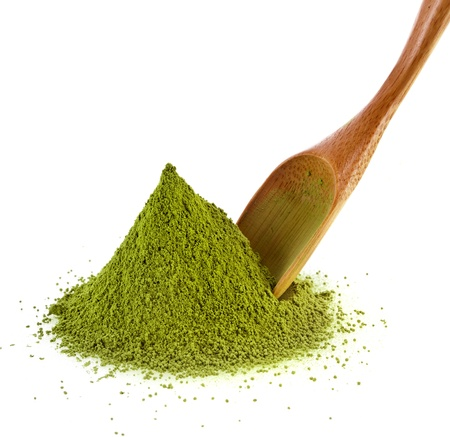 matcha: pile of powdered green tea with bamboo tea spoon , isolated on white background