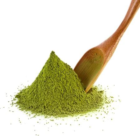 stapelen van gepoederde groene thee met bamboe thee lepel, geïsoleerd op witte achtergrond Stockfoto