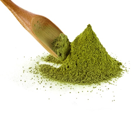green powder: pile of powdered green tea with bamboo tea spoon , isolated on white background
