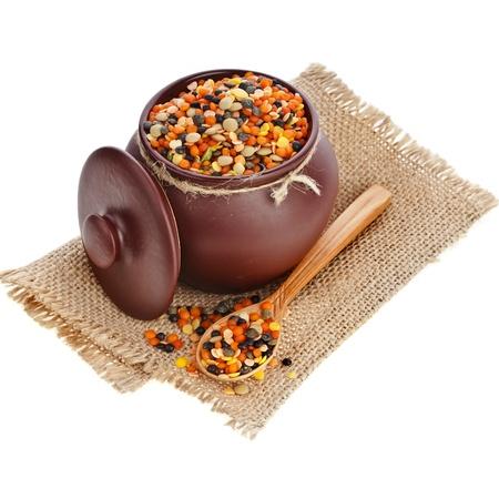 crock pot: crock pot lentil in sackcloth canvas burlap napkin isolated on white background Stock Photo