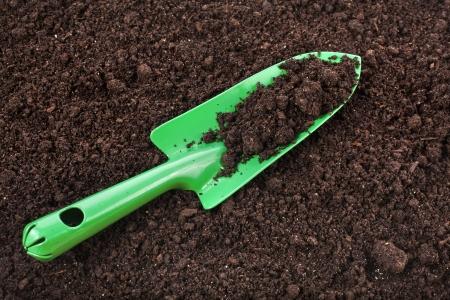 suelo arenoso: Primer plano de fondo de la superficie de suelo orgánico y herramienta de jardineria