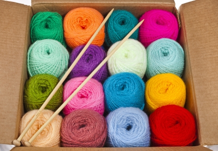 colorful different thread balls of knitting yarn in a cardboard box isolated on white background photo