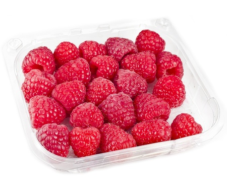 Ripe raspberries in plastic container box, isolated over a white background photo