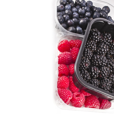 Border of Ripe BlackBerries in plastic container box, isolated over a white background photo