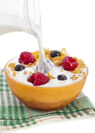 corn flakes with fresh berries and pouring splash milk isolated on white background photo