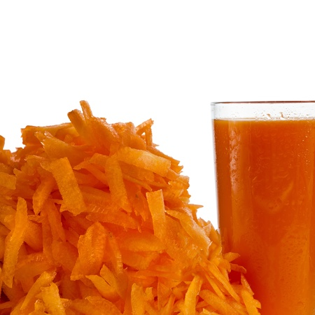 glass of carrot juice and heap carrots grated isolated on white photo