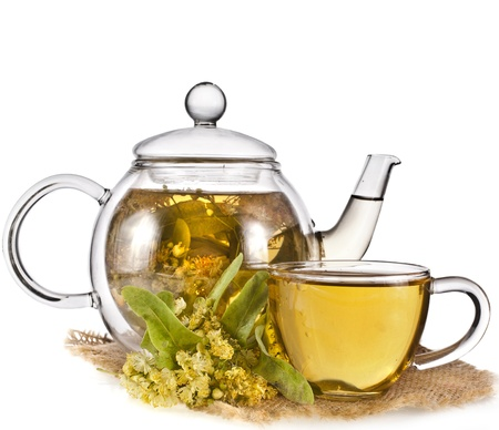 Tea pot with glass tea cup and linden bloom isolated on white background photo