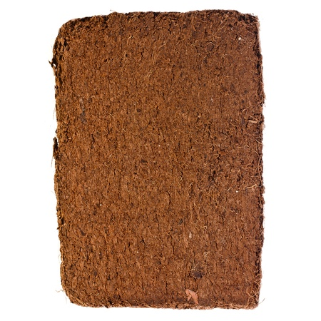 A compressed bale of ground coconut shell fibers  coir , surface background Stock Photo - 21365771