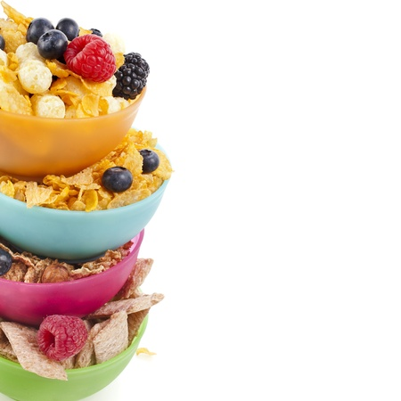 cornflakes: Border of corn flakes in colorful plastic bowl with fresh berries isolated on white background