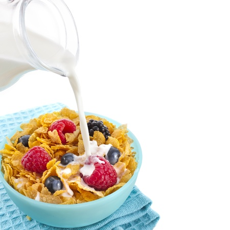 corn flakes with fresh berries and pouring milk isolated on white background photo