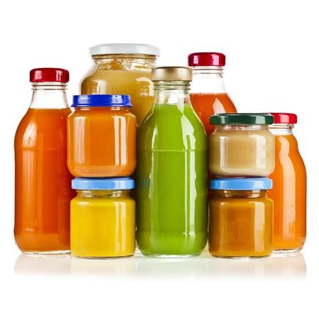 teteros: Botellas de cristal de varios colores jarra con jugo de frutas rojas frescas aisladas sobre fondo blanco Foto de archivo