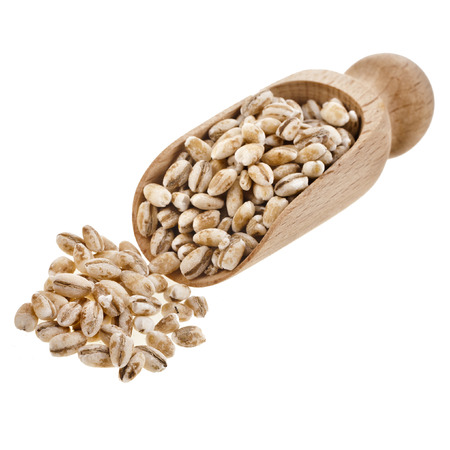pearl barley: pearl barley in a wooden scoop isolated on white background